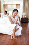 Upset lovers sitting on the bed separately Royalty Free Stock Images