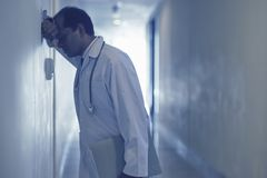 Upset doctor. Upset male doctor standing at corridor and leaning against the wall stock photos