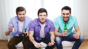 Upset male friends with beer watching tv at home. Friendship, sports and entertainment concept - upset male friends with beer watching tv and clinking at home stock video