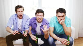 Upset male friends with beer watching tv at home. Friendship, sports and entertainment concept - upset male friends with beer watching tv and clinking at home stock footage