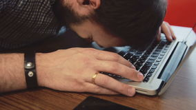 Upset man bangs his head on the laptop keyboard stock footage