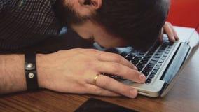 Upset man bangs his head on the laptop keyboard. Depression. Upset man bangs his head on the laptop keyboard stock footage