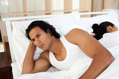 Upset man in bed sleeping separate of a woman Stock Photography