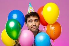 Upset man celebrating birthday, holding colorful baloons over purple background. Stock Photos