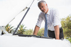 Upset man checking his car engine after breaking down Royalty Free Stock Photos