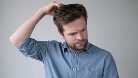 Upset man checking his head finding lice in his hair