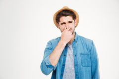 Upset man covered nose by hand and feeling bad smell Royalty Free Stock Photo
