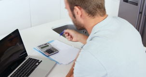 Upset man doing his accounting with a laptop stock footage