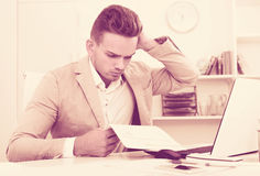 Upset  man having business problems with documents Royalty Free Stock Photography