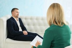 Upset man having consultation with female psychologist royalty free stock photos
