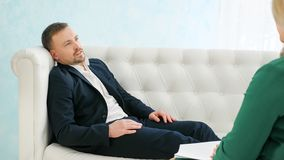 Upset man having consultation with female psychologist royalty free stock images