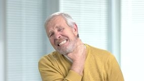 Upset man having terribe neck pain. Senior man suffering from neck strain and sprain. Deformations of the spine stock footage
