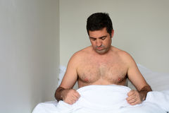 Upset man in his forties (40s) in bed looking down at his penis Royalty Free Stock Images