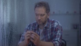 Upset man holding engagement ring on rainy day, divorce concept, family conflict. Stock footage stock footage