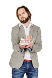 Upset man holding gift box, displeased with what he received, di Royalty Free Stock Photos