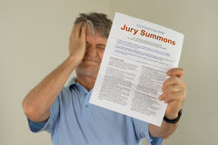 Upset man holding jury duty summons received in the mail. Angry upset man holding out his hand to show the jury duty summons he received in the mail which means royalty free stock images