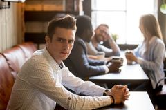Upset man jealous of multiracial friends having fun in cafe