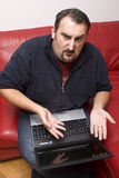 Upset man with laptop Stock Images