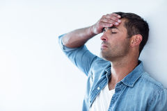 Upset man leaning on wall. Close-up of upset man leaning on wall with hand on forehead royalty free stock photos