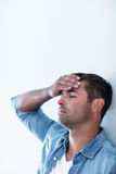 Upset man leaning on wall. Close-up of upset man leaning on wall with hand on forehead stock image