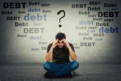 Upset man looking down thoughtful surrounded by huge debt amount royalty free stock photos
