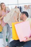 Upset man looking at his shopaholic girlfriend Royalty Free Stock Images