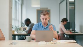 Upset man looking at laptop computer at workplace. Shocked man reading news. Online on notebook in office. Young man panic while looking at laptop at coworking stock video footage
