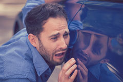 Upset man looking at scratches and dents on his car outdoors. Frustrated upset young man looking at scratches and dents on his car outdoors Royalty Free Stock Photo
