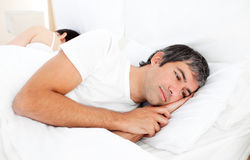 Upset man lying in his bed Stock Photography