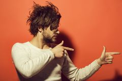 Upset man. product presentation, handsome man with beard and stylish hair. In white underwear with pointing fingers on red background, morning and fashion, copy royalty free stock photography