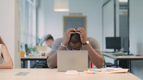 Upset man reading bad news on laptop computer at coworking space. Serious afro man stressed at office workplace. African male professional making mistake stock footage