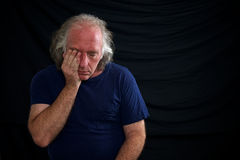 Upset man rubbing eye. A white man is rubbing his eye and looks sad against a black background and wearing a t shirt Royalty Free Stock Image