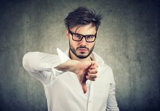 Upset man showing thumb up. Frowning man in eyeglasses holding thumb down looking at camera in dislike Stock Images