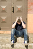 Upset man sits on the stairs. The upset man sits on the stairs near the house door Royalty Free Stock Photos