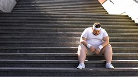 Upset man sitting alone on stairs, fighting with overweight and food addiction. Stock photo stock photo
