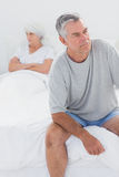 Upset man sitting on bed during a dispute Stock Images