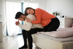 Upset man sitting on bed and his girlfriend hugging him stock image
