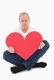 Upset man sitting holding heart shape Stock Photography