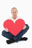 Upset man sitting holding heart shape Stock Photography