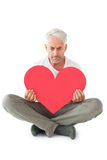Upset man sitting holding heart shape Stock Photo