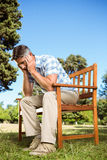 Upset man sitting on park bench Stock Images
