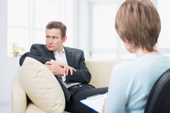 Upset man talking with psychologist Stock Image