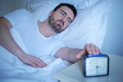 Upset man trying to sleep in his bed at night. Upset man trying to wake up from the bed Stock Photos