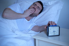 Upset man trying to sleep in his bed at night Royalty Free Stock Image