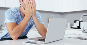 Upset man using laptop. In the kitchen stock video footage