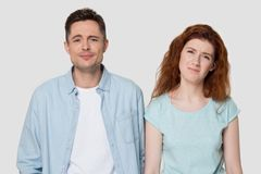 Upset man and woman feel down about unpleasant life situation. Disappointed millennial man and woman in casual clothes isolated on grey studio background unhappy stock photography