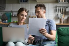 Upset man and woman using laptop, check documents. Upset men and women sitting together on sofa, using laptop, wife and husband checking documents, reading bad stock photo