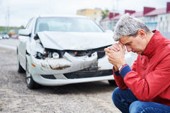 Upset man after wreck car crash. Upset driver man in front of wreck automobile after crash car collision accident in city road Royalty Free Stock Images