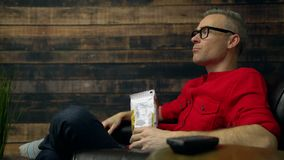 Upset man yells at TV while eating. Junk food chips stock video footage