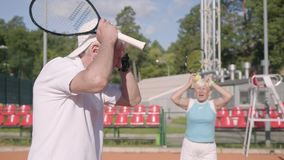 The upset mature couple lost the tournament on the tennis court. Senior man and woman holding the head with hands. The upset mature couple lost the tournament on stock video